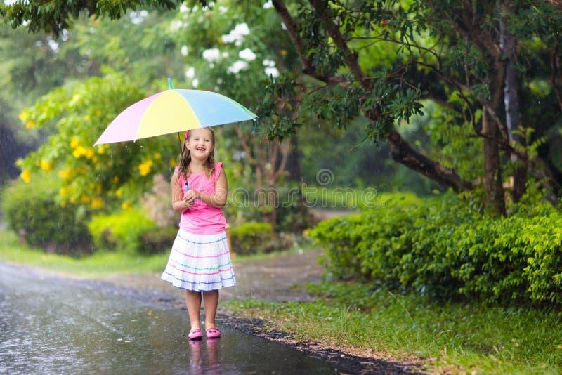 Jong geitje met paraplu het spelen in de zomerregen royalty-vrije stock afbeeldingen