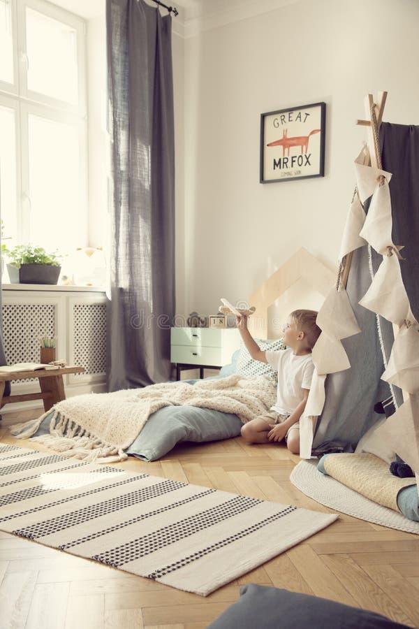 Jong geitje met stuk speelgoed vliegtuig in natuurlijke speelkamer met comfortabel bed en Skandinavische tent, echte foto stock foto's