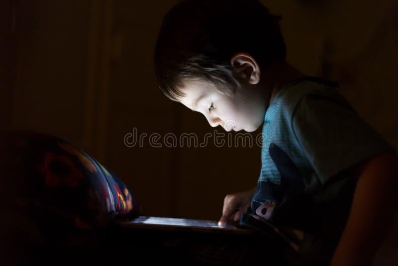 Jong geitje met tablet in dark stock afbeelding