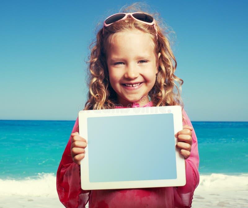 Jong geitje op het strand met tabletpc royalty-vrije stock fotografie