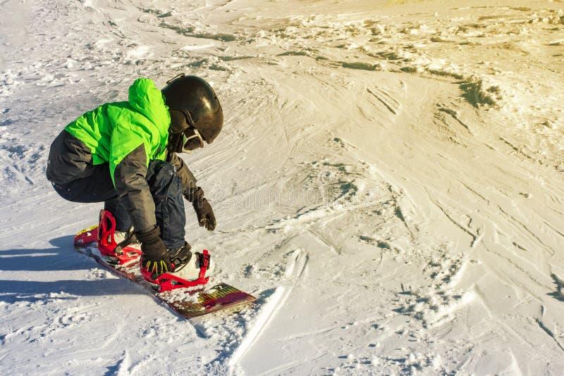 Jong geitje op snowboard in de aard van de de winterzonsondergang De sportfoto met geeft ruimte uit royalty-vrije stock foto's
