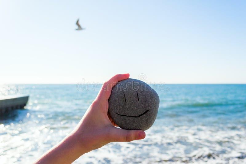 Jong geitje` s hand die een steen met het glimlachen gezicht naast het overzees in zonnige dag houden stock afbeeldingen