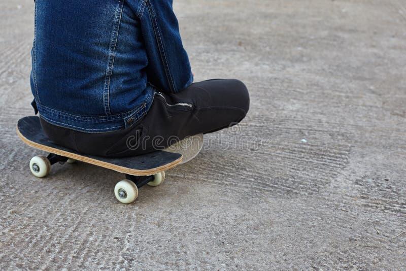 Jong geitje skateboarder zitting op zijn skateboard royalty-vrije stock foto