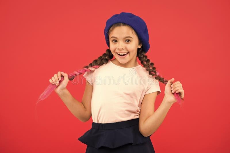 Jong geitje weinig het leuke meisje het glimlachen gezicht stellen op hoeden rode achtergrond Hoe te om Franse baret te dragen De stock foto