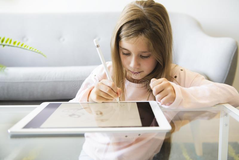 Jong geitje in woonkamer thuis en gebruikend digitale te trekken tablet stock foto's
