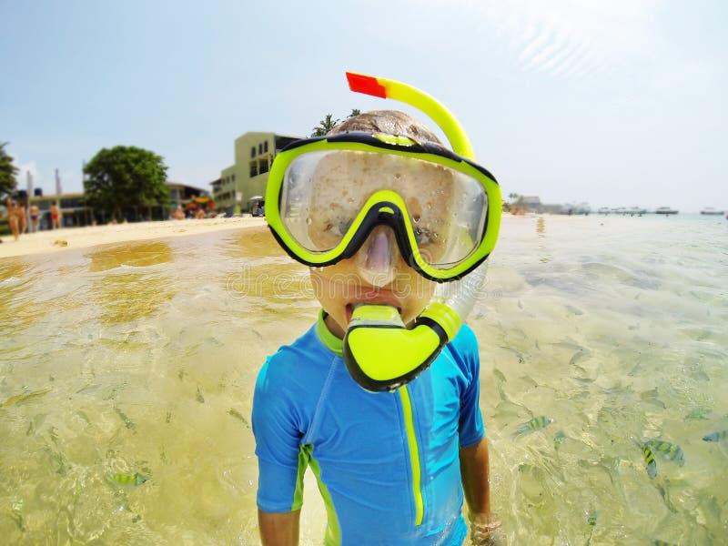 Jong geitje in zwemmend kostuum die in de Indische Oceaan snorkelen stock foto's