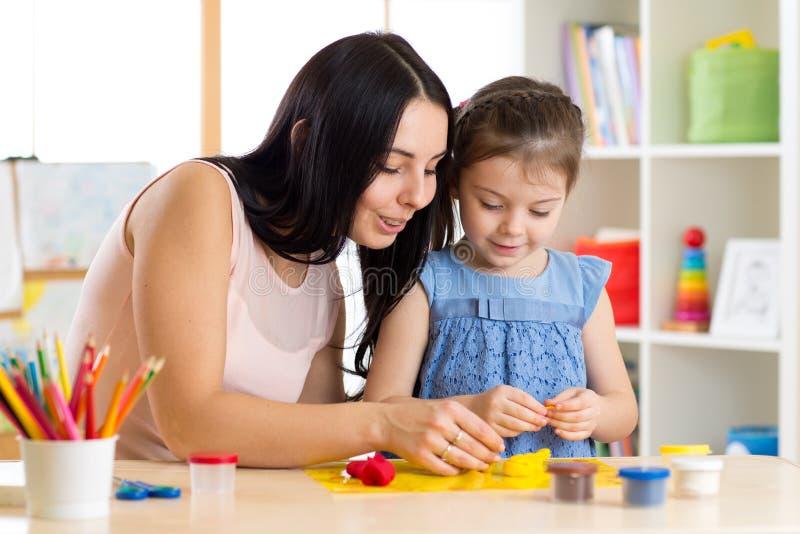 Jong geitjecreativiteit Kindmeisje met haar moeder die van spelklei beeldhouwen royalty-vrije stock afbeeldingen