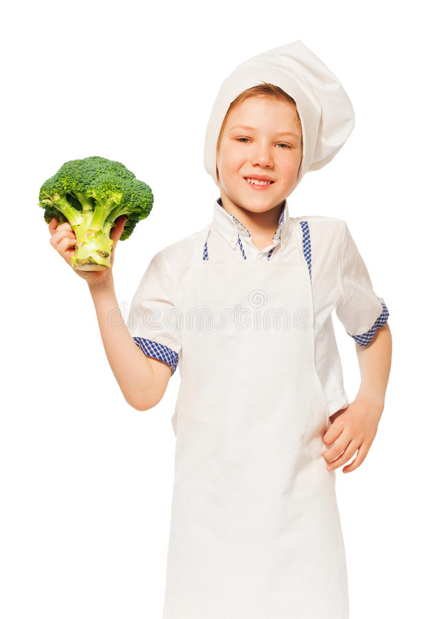 Jong geitjejongen in de schort van de kok en toque holdingsbroccoli stock afbeeldingen