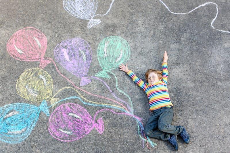 Jong geitjejongen die pret met kleurrijke ballons hebben die met krijt trekken stock fotografie