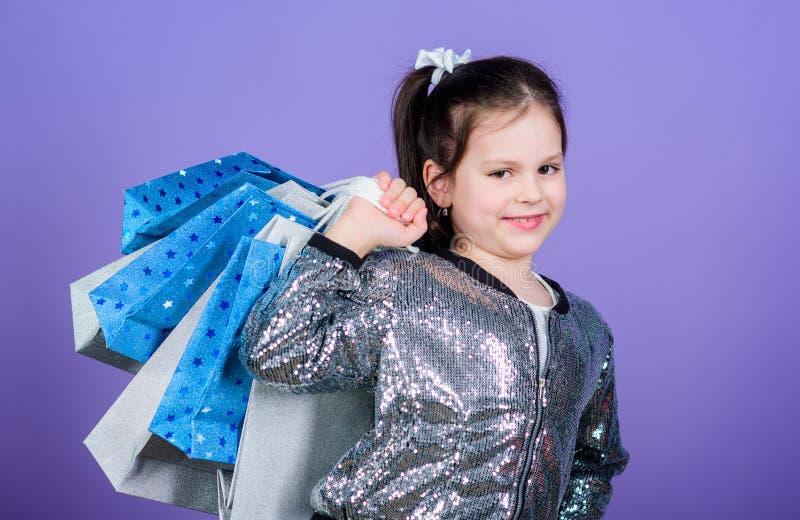 jong geitjemanier winkelmedewerker met pakket Gelukkig Kind Meisje met giften Verkoop en Kortingen Klein meisje met stock fotografie
