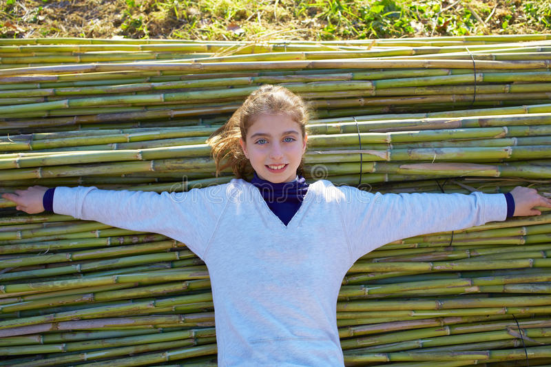 Jong geitjemeisje dat op groene rietachtergrond wordt ontspannen stock afbeelding