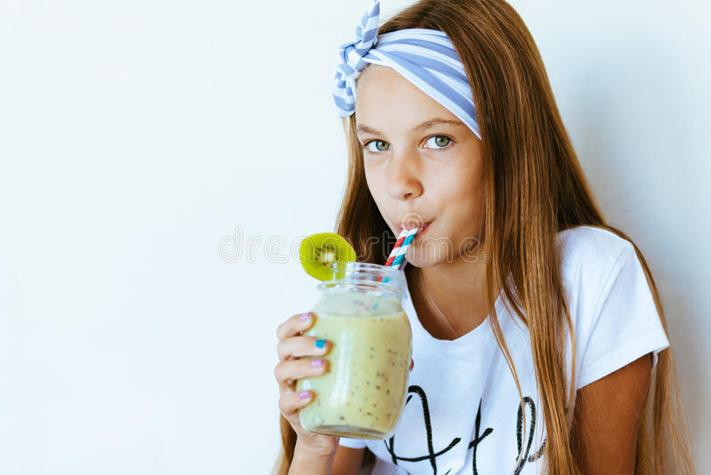 Jong geitjemeisje die smoothie drinken stock foto