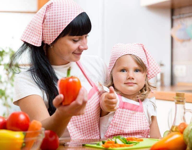 Jong geitjemeisje met mamma die duim op keuken tonen royalty-vrije stock afbeelding
