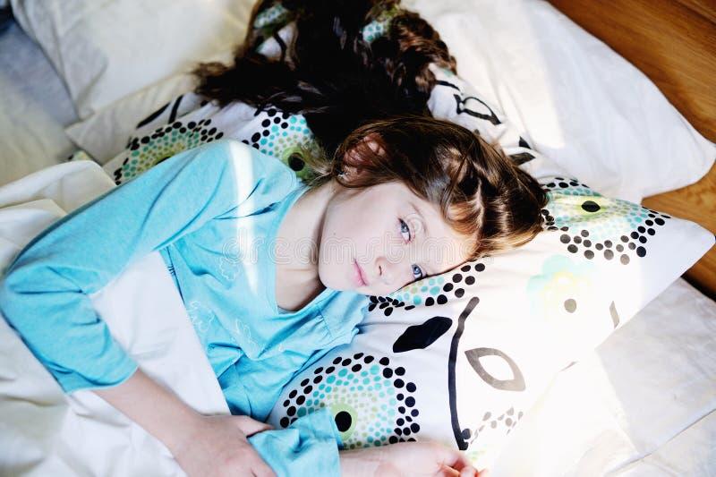 Jong geitjemeisje op bed in de slaapkamer stock afbeeldingen