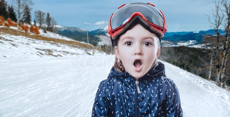 Jong geitjemeisje in skitoestel op de winterachtergrond stock afbeeldingen