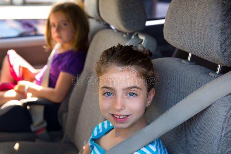 Jong geitjemeisjes met veiligheidsgordel in auto binnen stock afbeelding