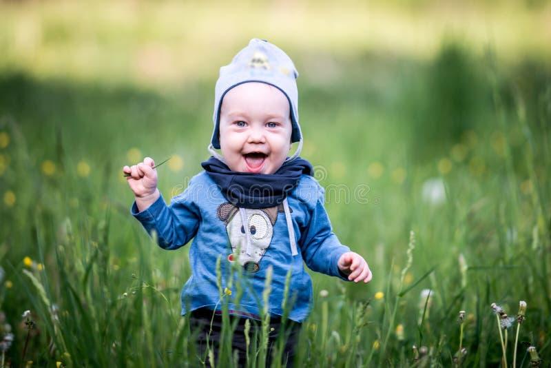 Jong geitjepeuter in gras, gelukkige uitdrukking royalty-vrije stock foto