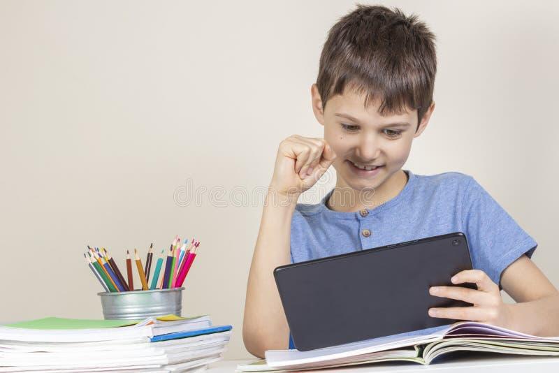 Jong geitjezitting bij lijst met boekennotitieboekjes en speelspelen op tabletcomputer stock foto