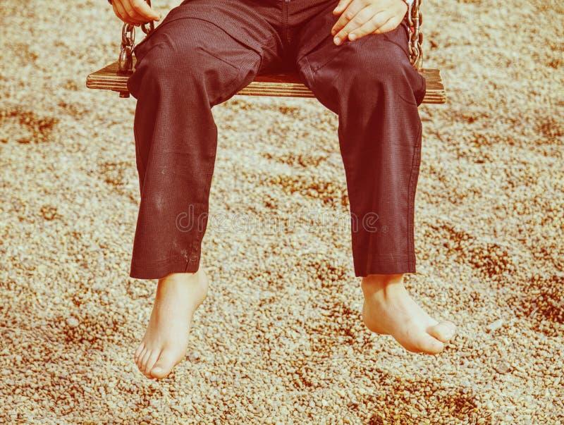Jong geitjezitting met voeten tegen een zand in de zomerspeelplaats stock foto's