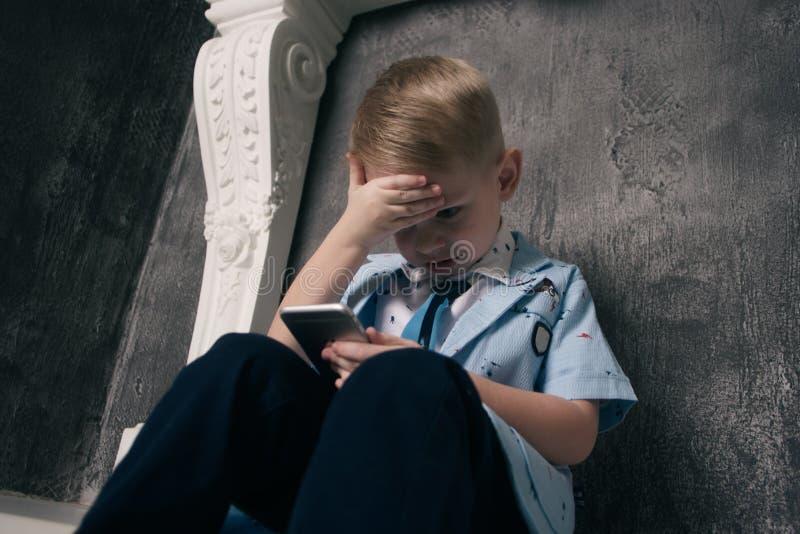 Jong geitjezitting op de vloer en het spelen met slimme telefoon royalty-vrije stock afbeelding