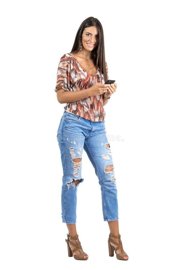 Jong gelooid Indisch schoonheid het typen bericht op haar mobiele telefoon die camera bekijken stock fotografie