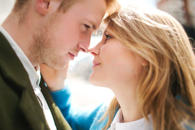 Jong gelukkig blondepaar die en op stadsstraat kussen koesteren stock foto's