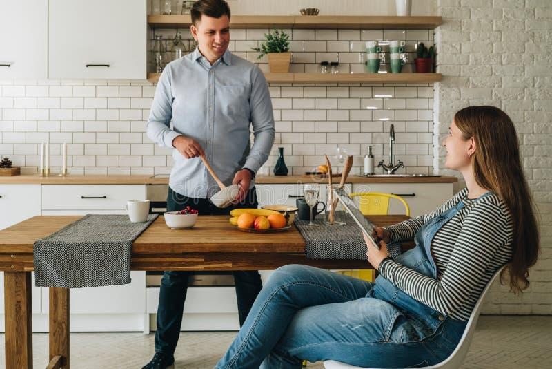 Jong gelukkig echtpaar in keuken De mens bevindt zich door keukenlijst en bereidt ontbijt voor de Zwangere vrouw zit stock afbeeldingen