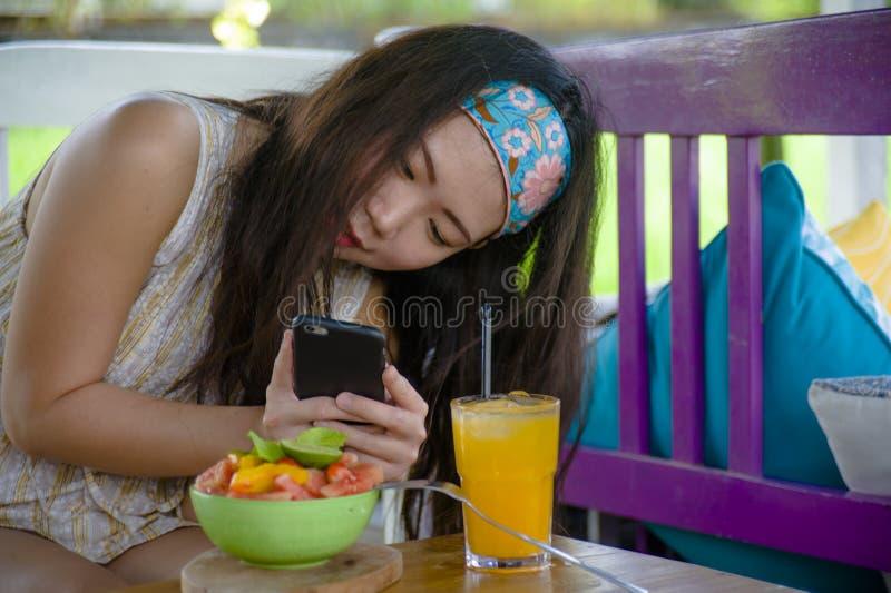 Jong gelukkig en vrij digitaal nomade Aziatisch Koreaans meisje die beeld van fruitsalade met mobiel telefoonvoorzien van een net royalty-vrije stock afbeeldingen