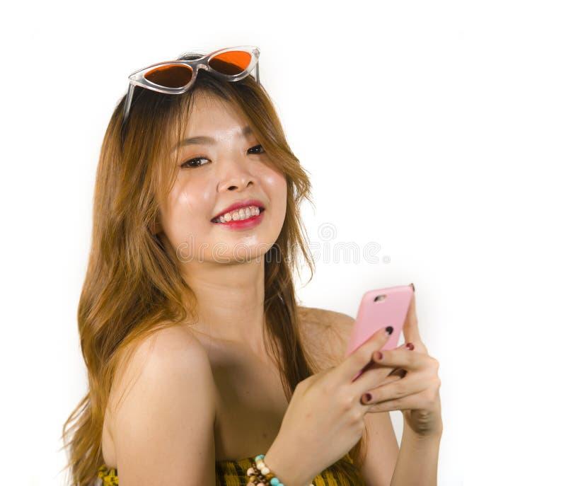 Jong gelukkig en vrolijk Aziatisch Koreaans meisje met manierzonnebril en het sexy hoogste holdings mobiele telefoon online dater stock afbeelding