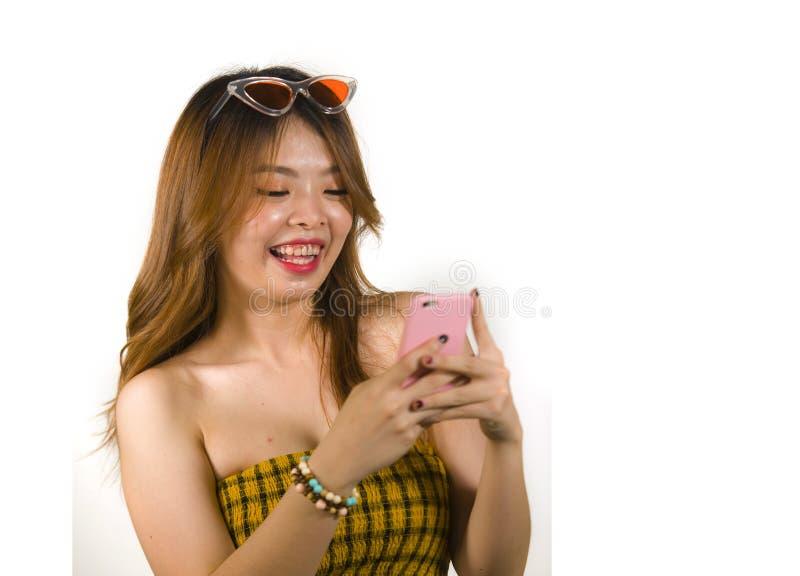 Jong gelukkig en vrolijk Aziatisch Koreaans meisje met manierzonnebril en het sexy hoogste holdings mobiele telefoon online dater stock fotografie