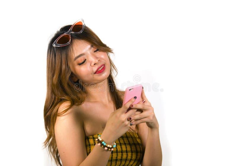 Jong gelukkig en vrolijk Aziatisch Koreaans meisje met manierzonnebril en het sexy hoogste holdings mobiele telefoon online dater stock foto's