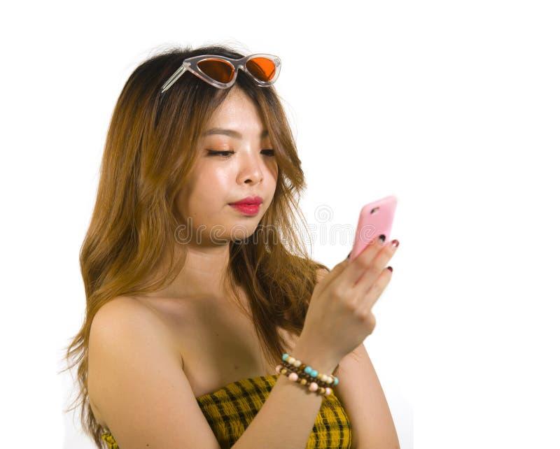 Jong gelukkig en vrolijk Aziatisch Koreaans meisje met manierzonnebril en het sexy hoogste holdings mobiele telefoon online dater royalty-vrije stock foto