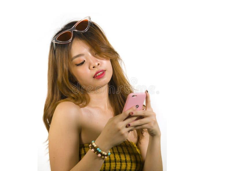 Jong gelukkig en vrolijk Aziatisch Koreaans meisje met manierzonnebril en het sexy hoogste holdings mobiele telefoon online dater royalty-vrije stock foto's