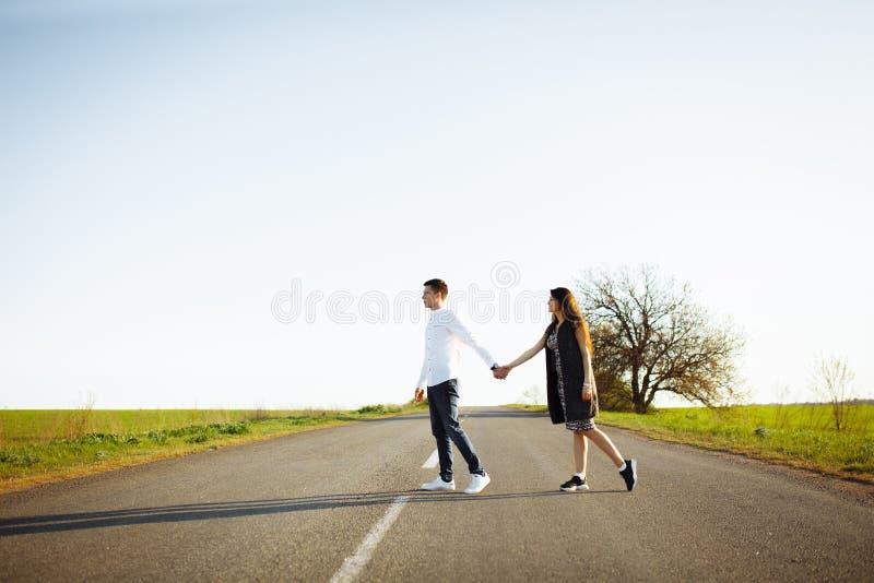 Jong, gelukkig, houdend van paar die zich op de handen van de wegholding bevinden en elkaar bekijken, en tekst adverteren opnemen royalty-vrije stock afbeelding