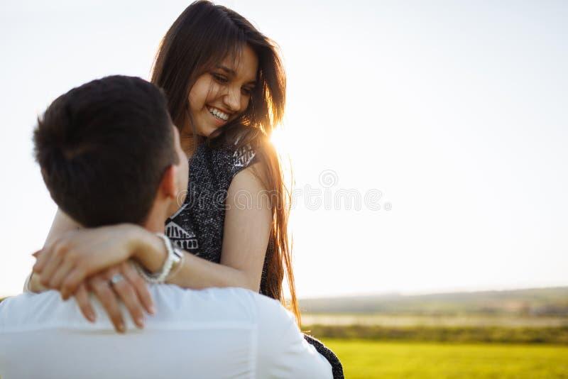 Jong, gelukkig, houdend van paar, in openlucht, mens die een meisje in zijn wapens houden, en van elkaar genieten, en tekst adver royalty-vrije stock foto's