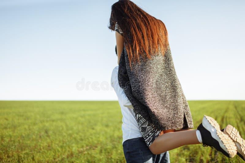 Jong, gelukkig, houdend van paar, in openlucht, mens die een meisje in zijn wapens houden, en van elkaar genieten, en tekst adver stock foto's
