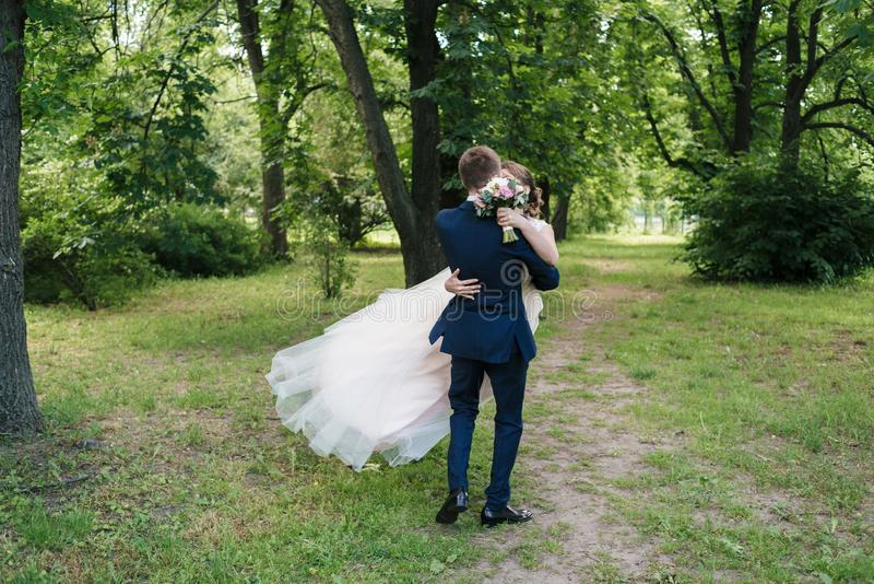 Jong gelukkig huwelijkspaar die en pret in zonnige huwelijksdag dansen hebben Bruidegom Spinning Bride de kleding ontwikkelt zich stock afbeeldingen