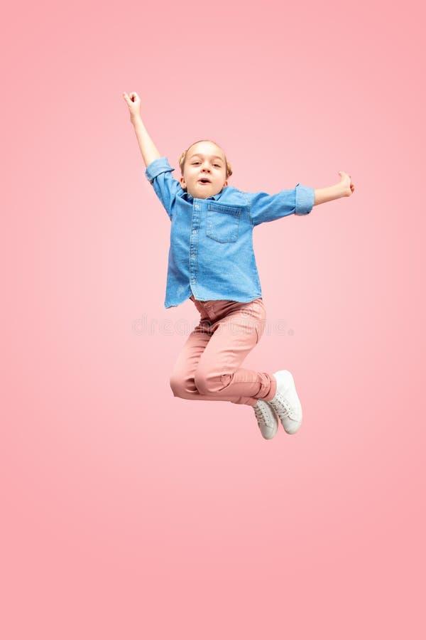 Jong gelukkig Kaukasisch tienermeisje die die in de lucht springen, op roze studioachtergrond wordt geïsoleerd stock afbeelding