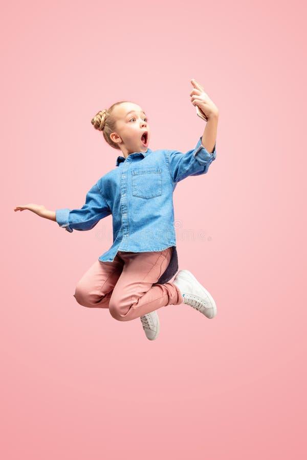 Jong gelukkig Kaukasisch tienermeisje die die met telefoon in de lucht springen, op roze studioachtergrond wordt geïsoleerd stock afbeeldingen