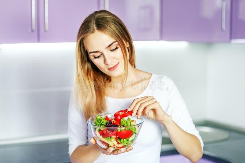 Jong gelukkig meisje die plantaardige de lentesalade eten Het concept is stock foto