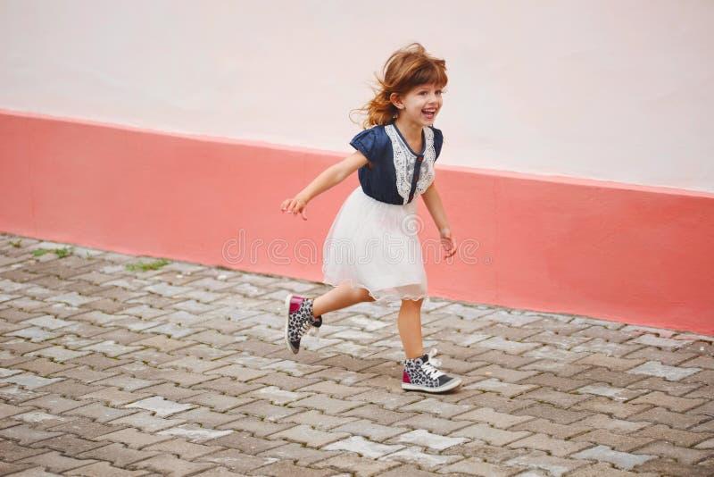 Jong gelukkig meisje die weglopen stock afbeeldingen