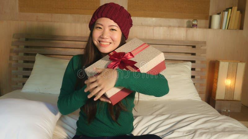 Jong gelukkig mooi Aziatisch Amerikaans meisje in de holdingskerstmis van de de winterhoed giftbox met lint die opgewekte en vrol stock fotografie