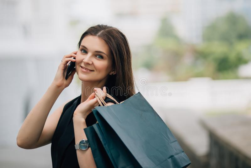 Jong gelukkig mooi Kaukasisch vrouwenbrunette met het winkelen zakken die haar smartphone gebruiken royalty-vrije stock foto