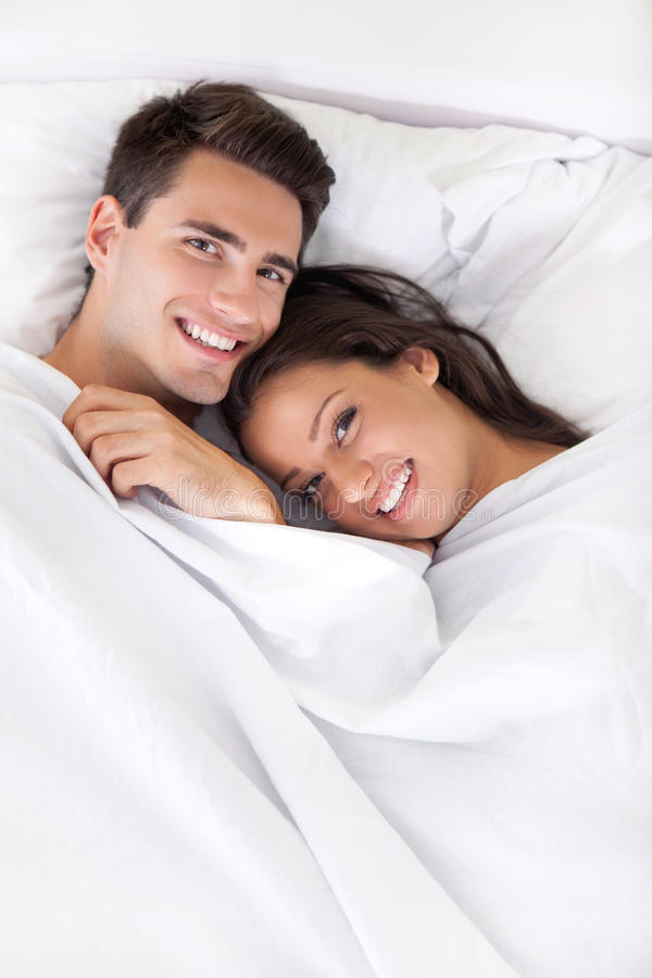 Jong gelukkig paar in bed royalty-vrije stock fotografie
