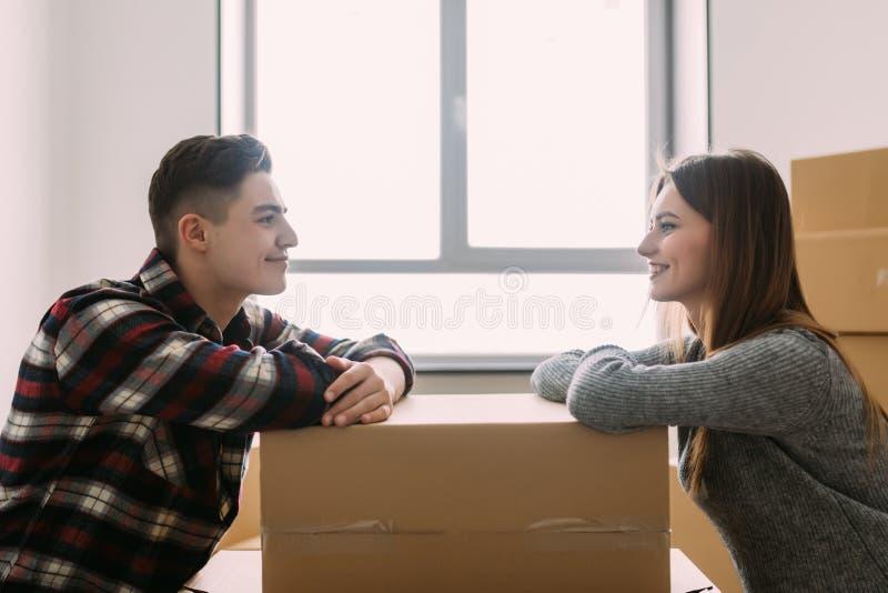 Jong gelukkig paar bewegend huis die elkaar die op een doos leunen kijken royalty-vrije stock afbeeldingen