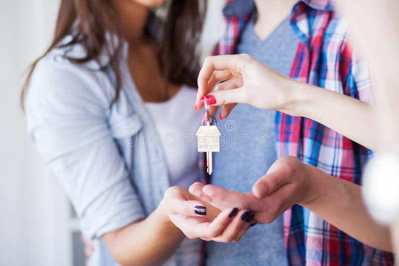 Jong gelukkig paar dat zich in hun nieuw huis beweegt Zij die en nieuw huis uitpakken schoonmaken stock foto's