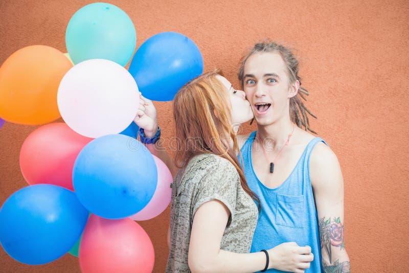 Jong gelukkig paar dichtbij de oranje muurtribune met ballons stock fotografie
