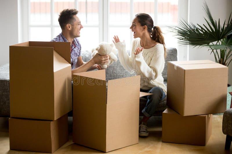 Jong gelukkig paar die de dozen van de pretverpakking in nieuw huis hebben stock foto's