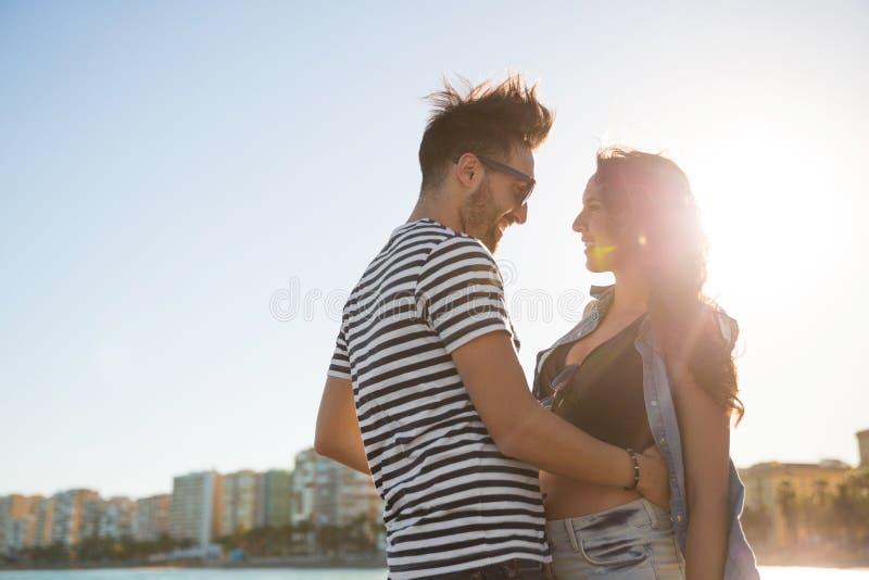 Jong gelukkig paar die elkaar buiten bekijken stock afbeeldingen