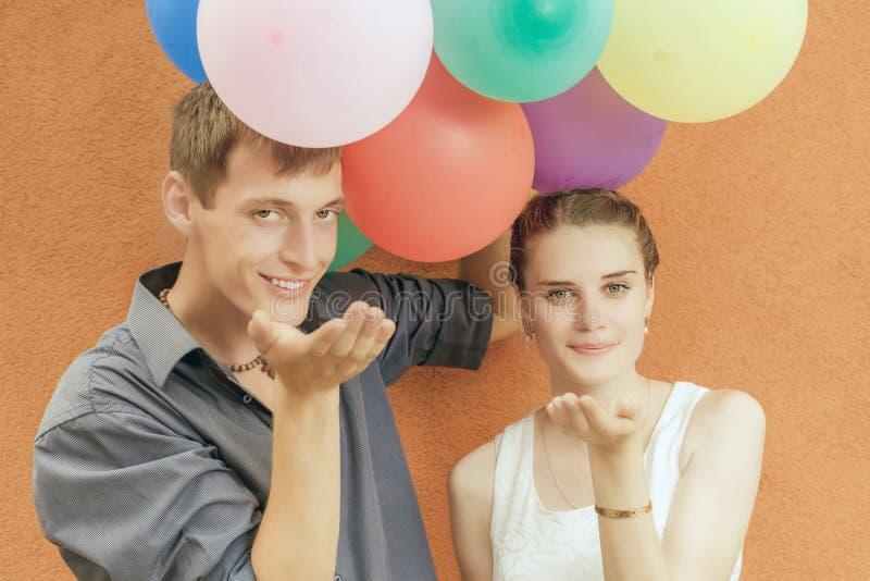 Jong gelukkig paar die en ballons kussen houden stock fotografie